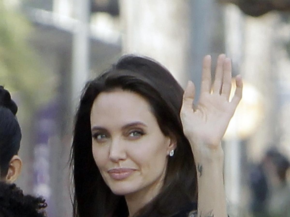 Angelina Jolie w czarnej sukience z koronką na dekolcie macha ręką