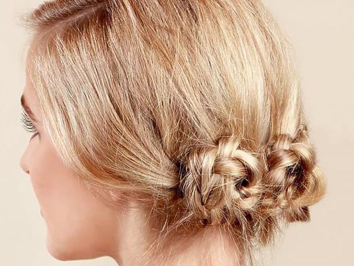 Blond włosy związane nad karkiem we fryzurę z zaplatanymi koczkami