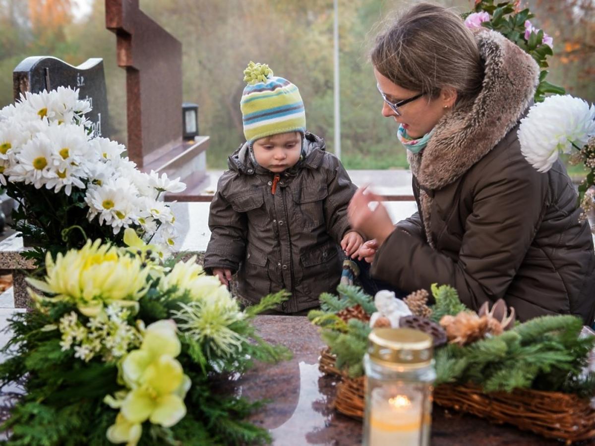 cmentarz - kobieta z dzieckiem na cmentarzu