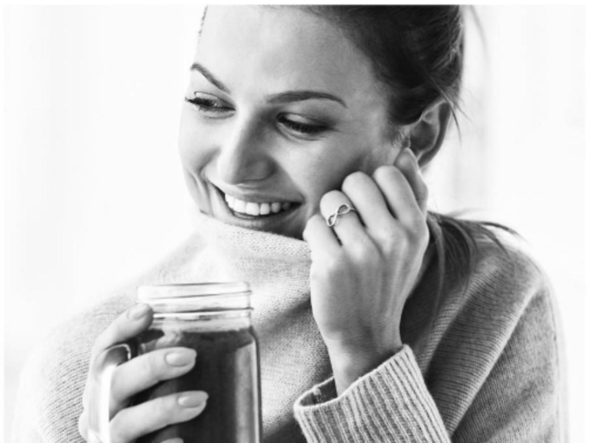 Czarno-białe zdjęcie Anny Lewandowskiej w swetrze, która trzyma kubek