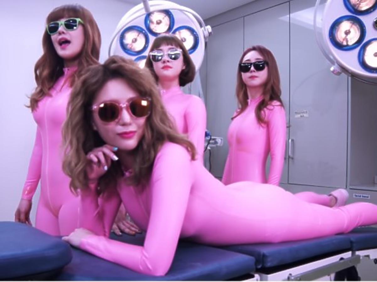 cztery koreanki na stole operacyjnym w ciemnych okularach i różowych kombinezonach six bomb