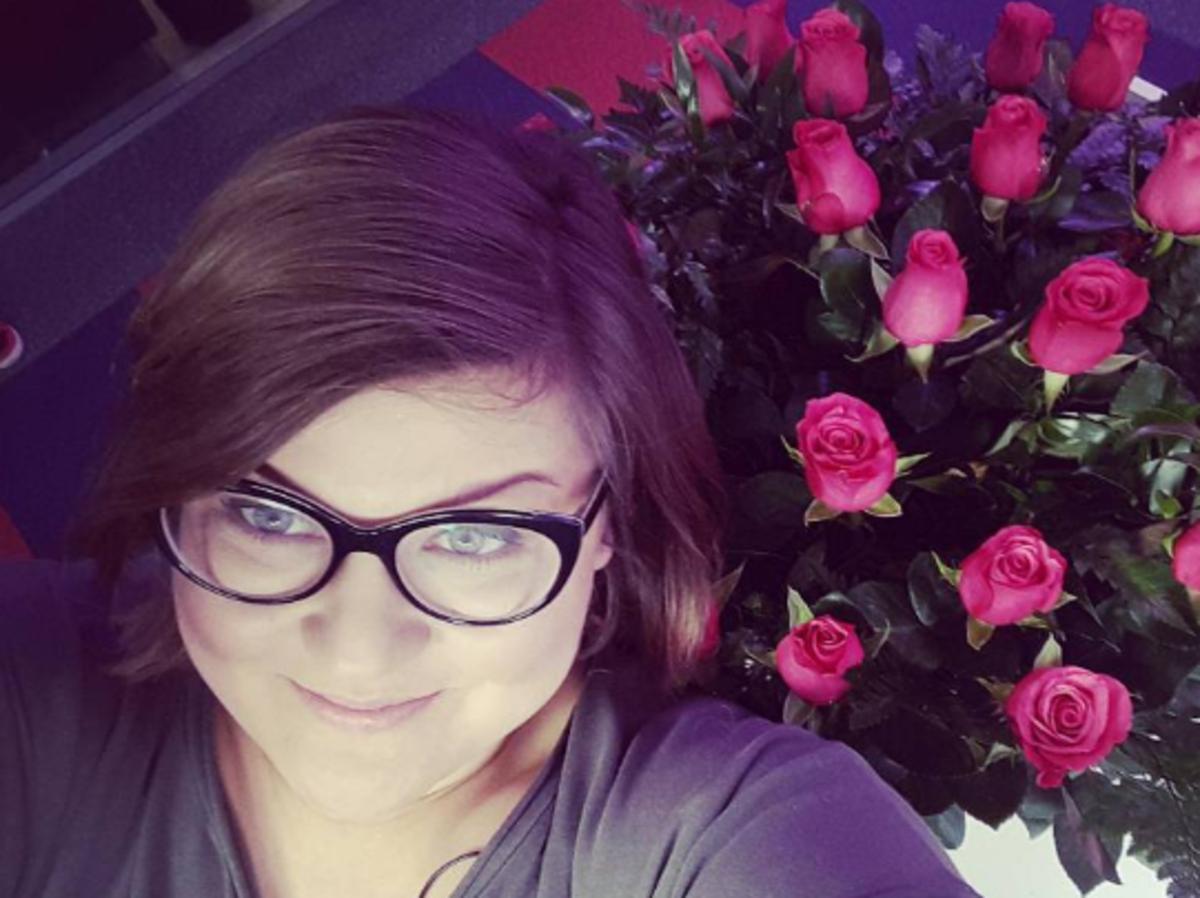 Dominika Gwit brunetka w okularach selfie z różami w tle