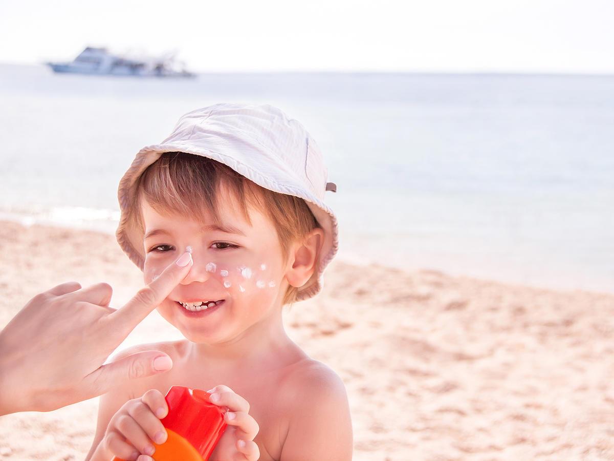 Dziecko na plaży, które ma aplikowany na nos krem przeciwsłoneczny