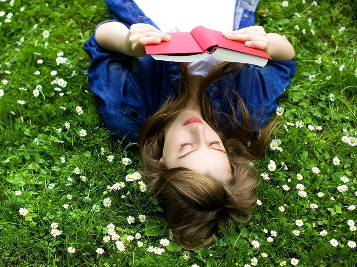 dziewczyna czyta książkę na trawie wśród kwiatów