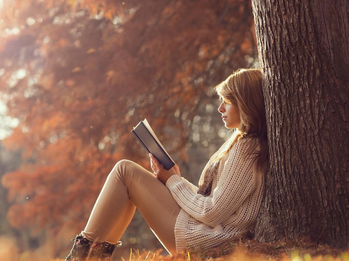 dziewczyna czyta książkę w jesiennym parku