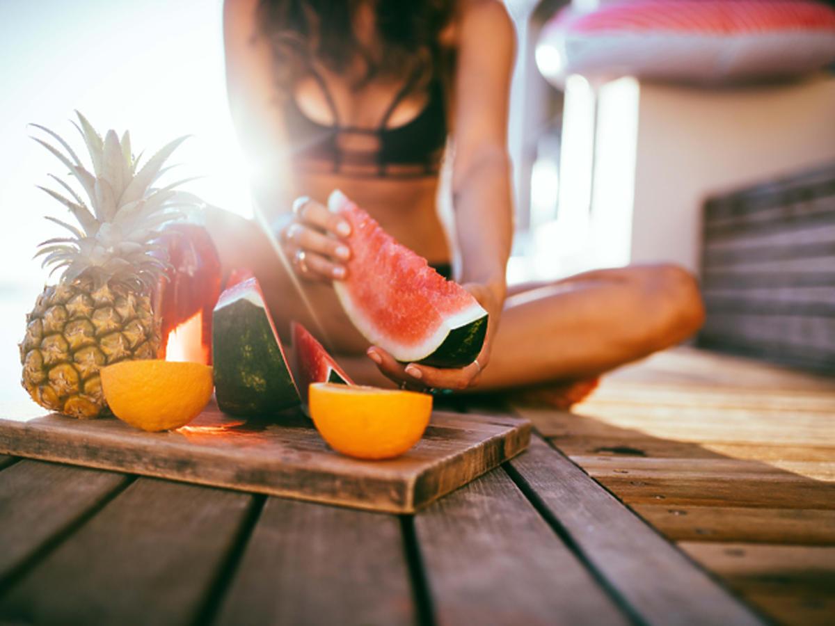 Dziewczyna trzyma w ręce arbuza obok tacy owoców i szklanek z sokiem