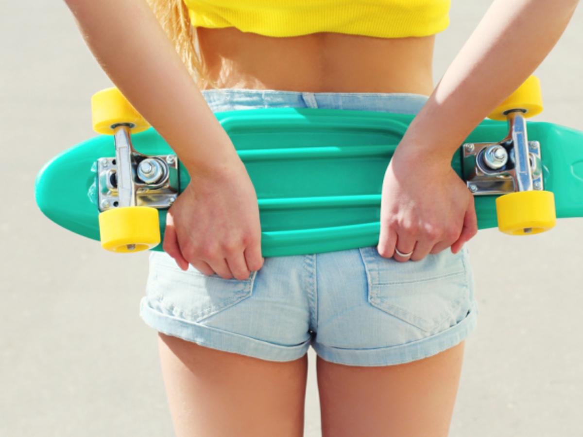 dziewczyna trzymająca za plecami deskorolkę w krótkich szortach
