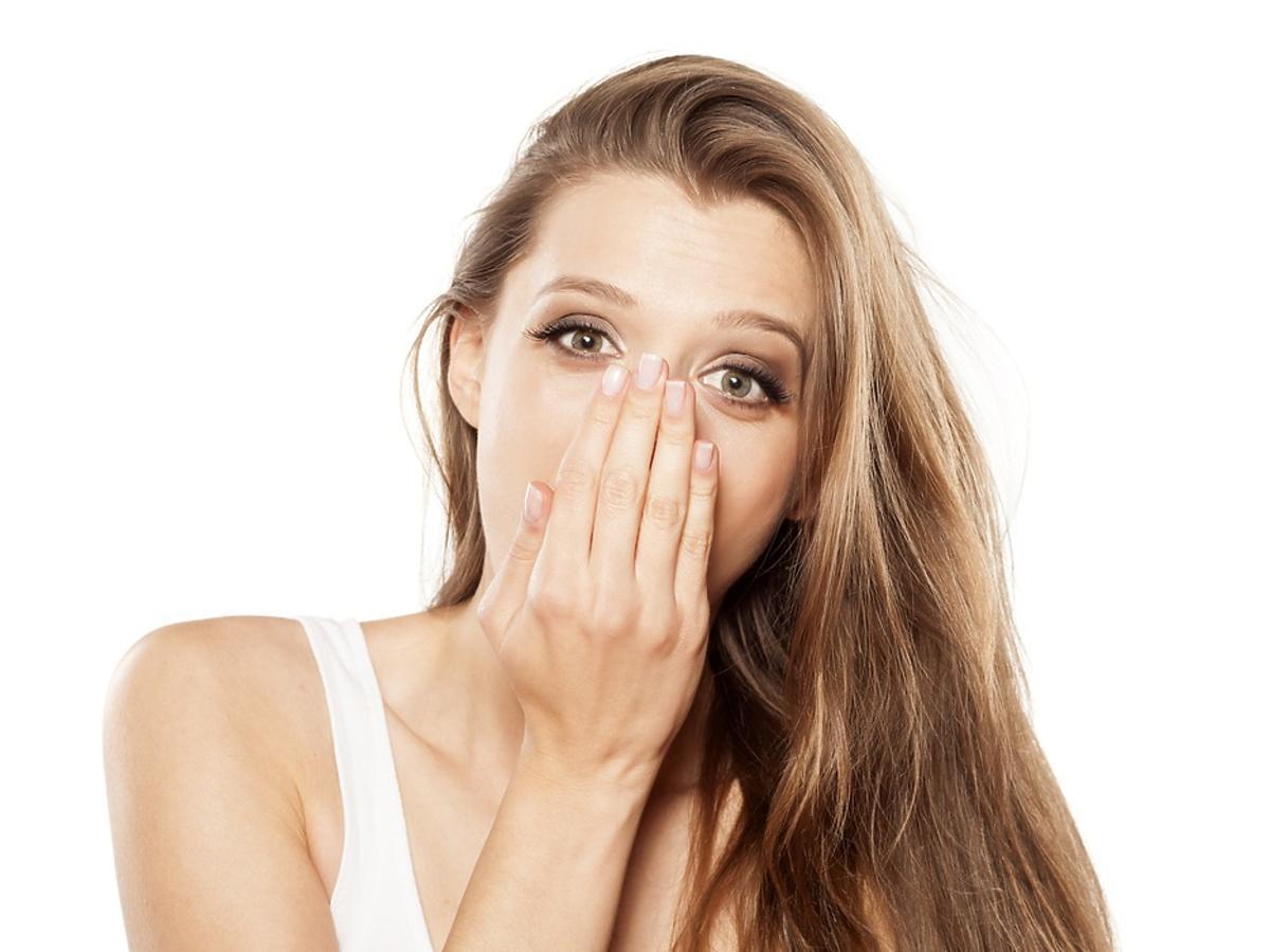 Dziewczyna w białej koszulce z zasłoniętymi ręką ustami