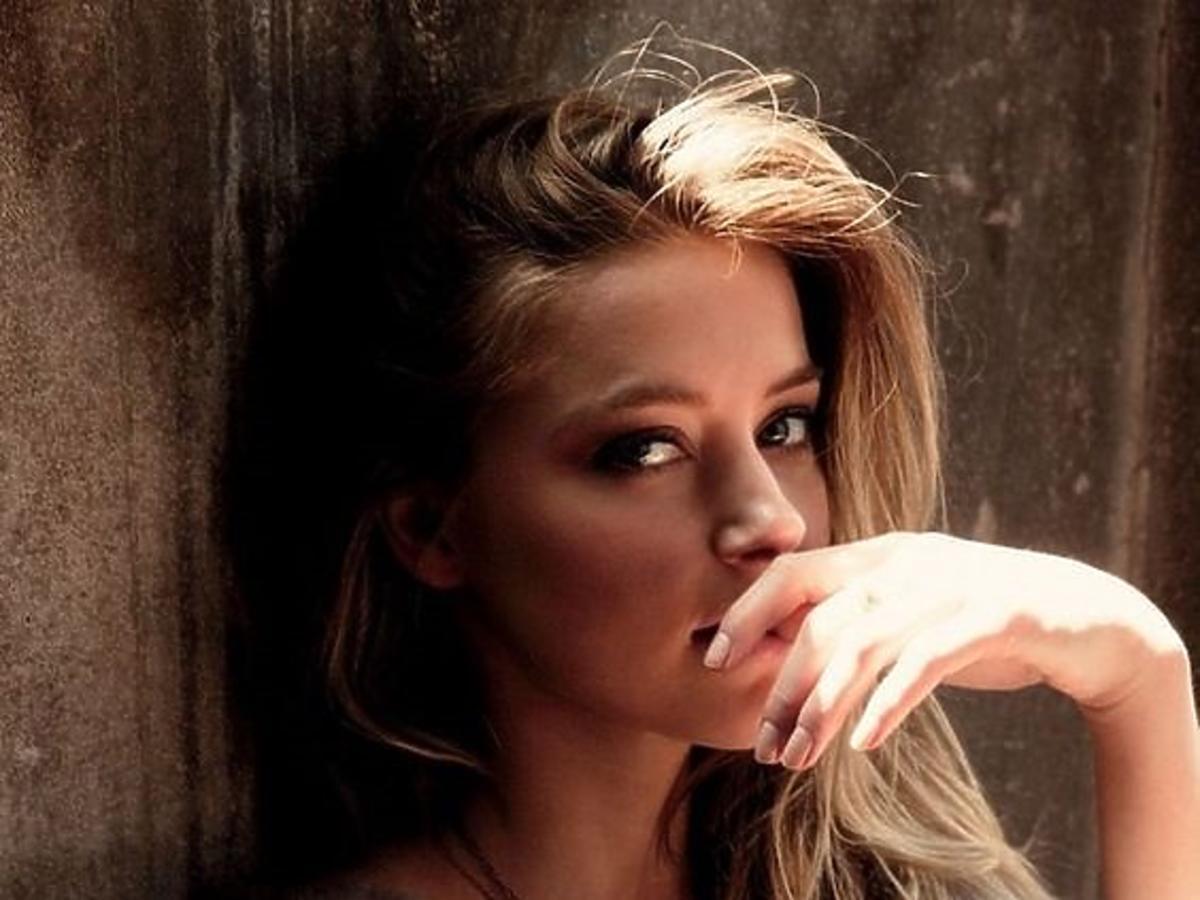 Dziewczyna w blond włosach i szarym swetrze opiera się o ścianę i trzyma dłoń przy ustach