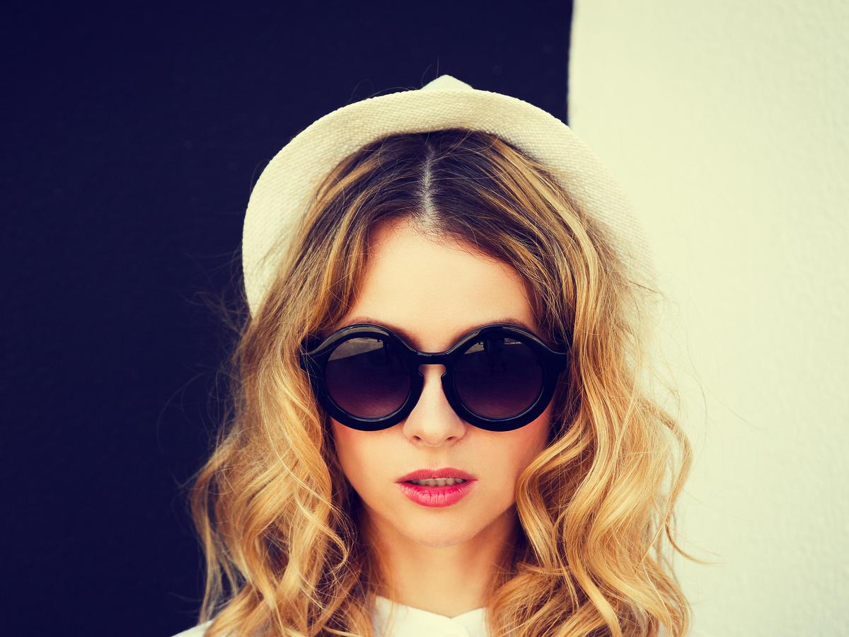Dziewczyna w czarnych okularach, białym kapeluszu i białej bluzce pozuje w rozpuszczonych blond włosach na czarno-białym tle