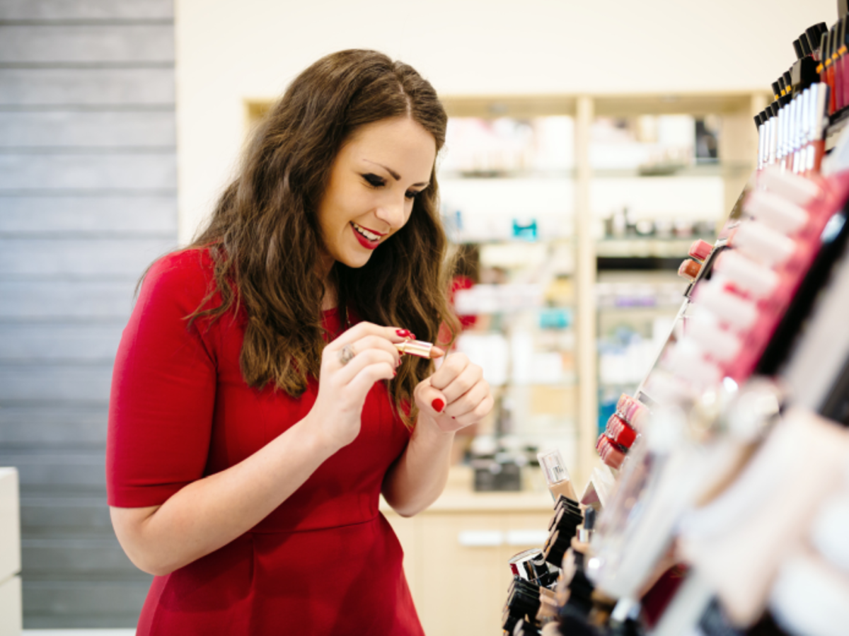 dziewczyna w czerwonej sukience testuje szminkę