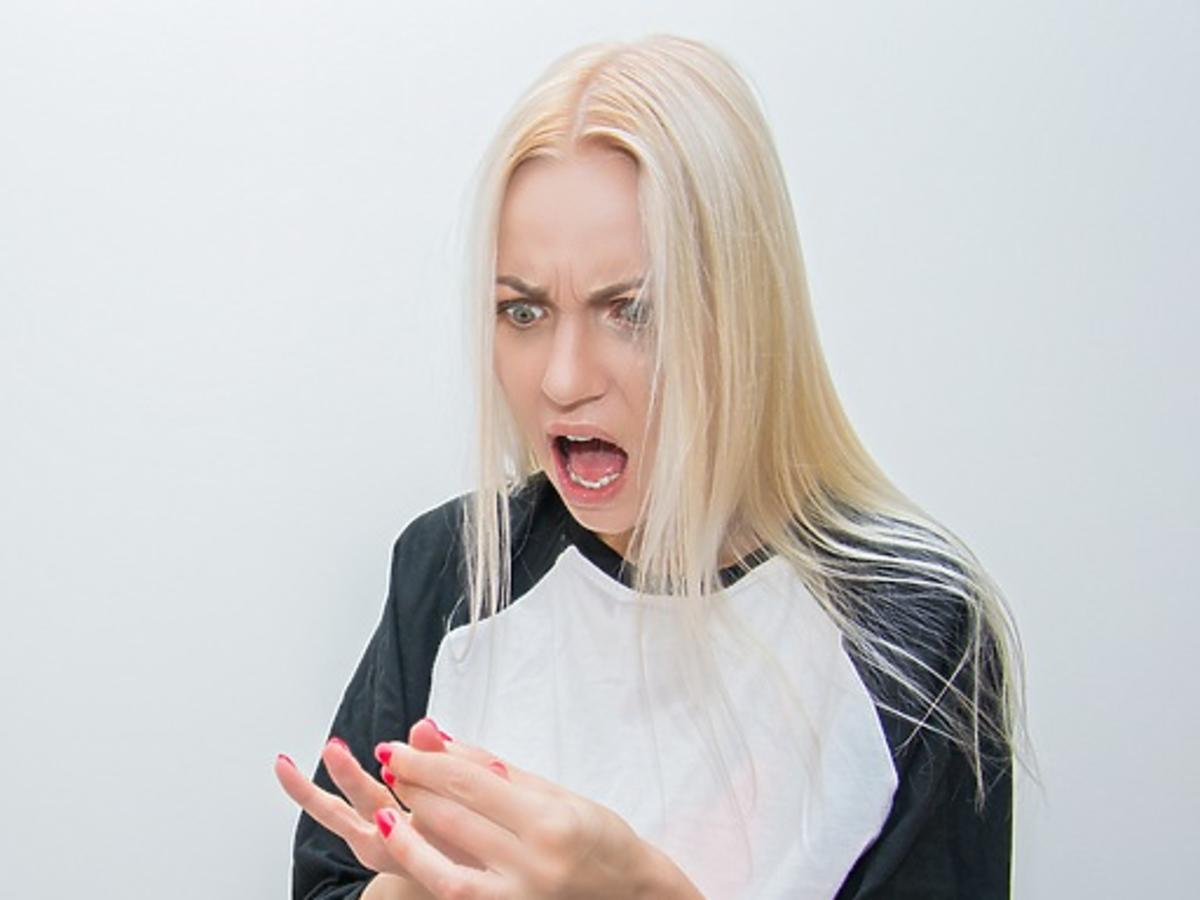 Dziewczyna w długich blond włosach patrzy na paznokcie i krzyczy