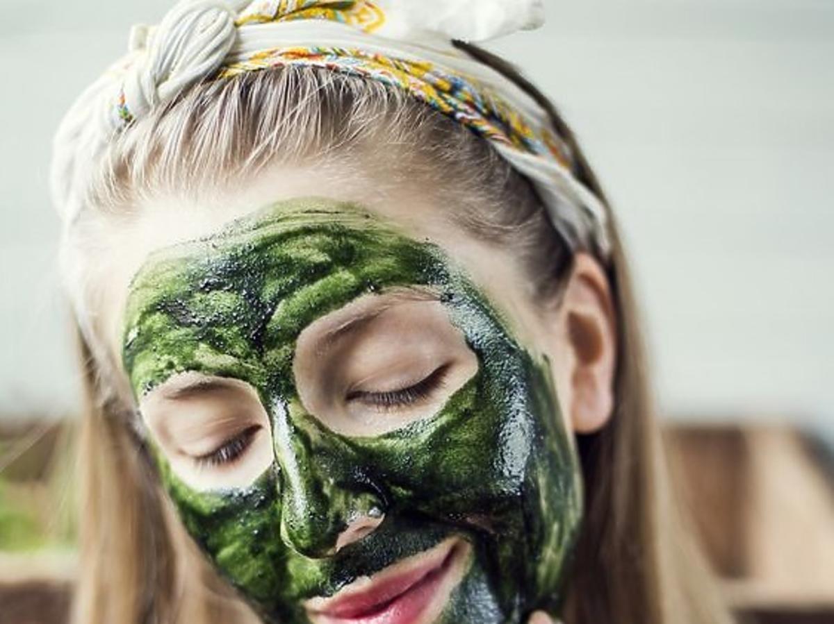 dziewczyna w zielonej masce do twarzy ze spiruliny