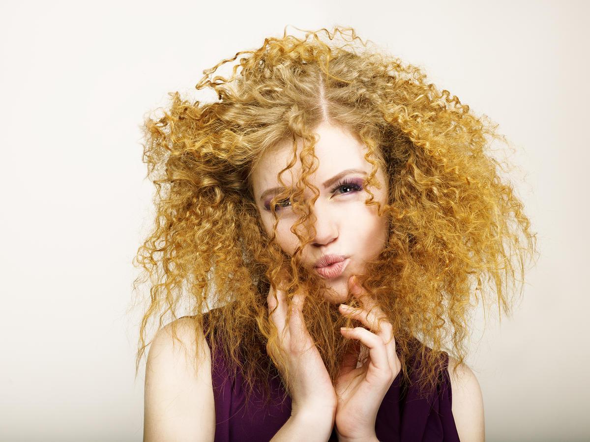 Dziewczyna z burzą blond-rudych loków i fioletowej bluzce bez rękawów trzyma dłonie blisko twarzy