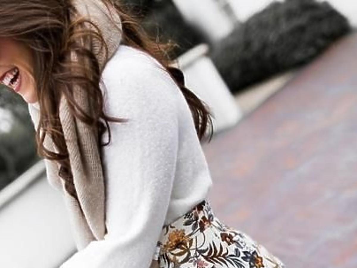 Dziewczyna z długimi brązowymi włosami w białym swetrze z szerokimi rękawami, rozkloszowanej spódniczce w kwiatki oraz szarych kozakach za kolano