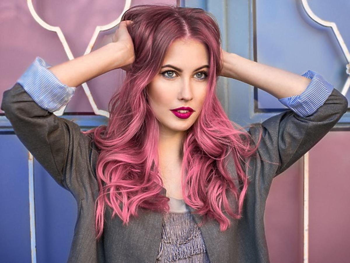 Dziewczyna z długimi, falowanymi, różowymi włosami trzyma dłonie na głowie