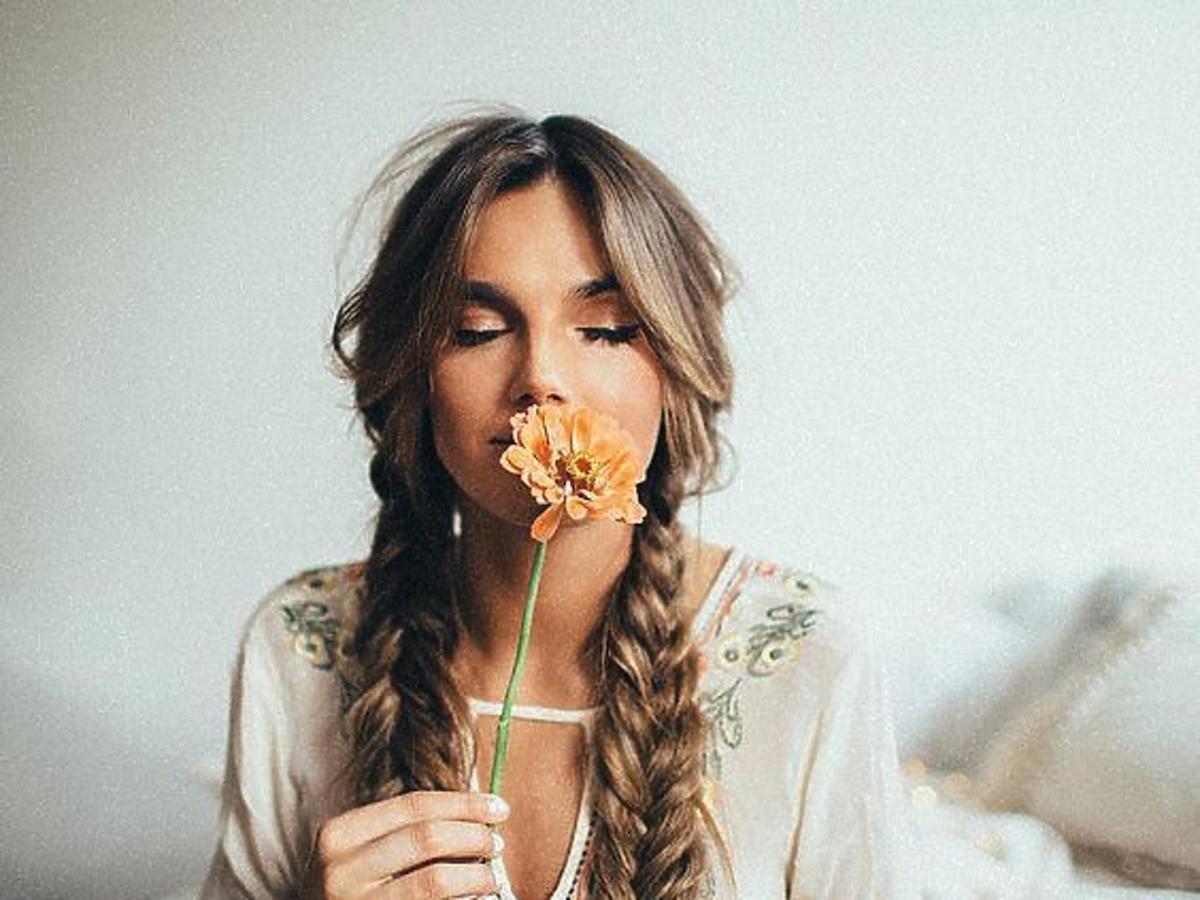 Dziewczyna z dwoma długimi warkoczami w kwiecistej sukience wącha żółtego kwiatka