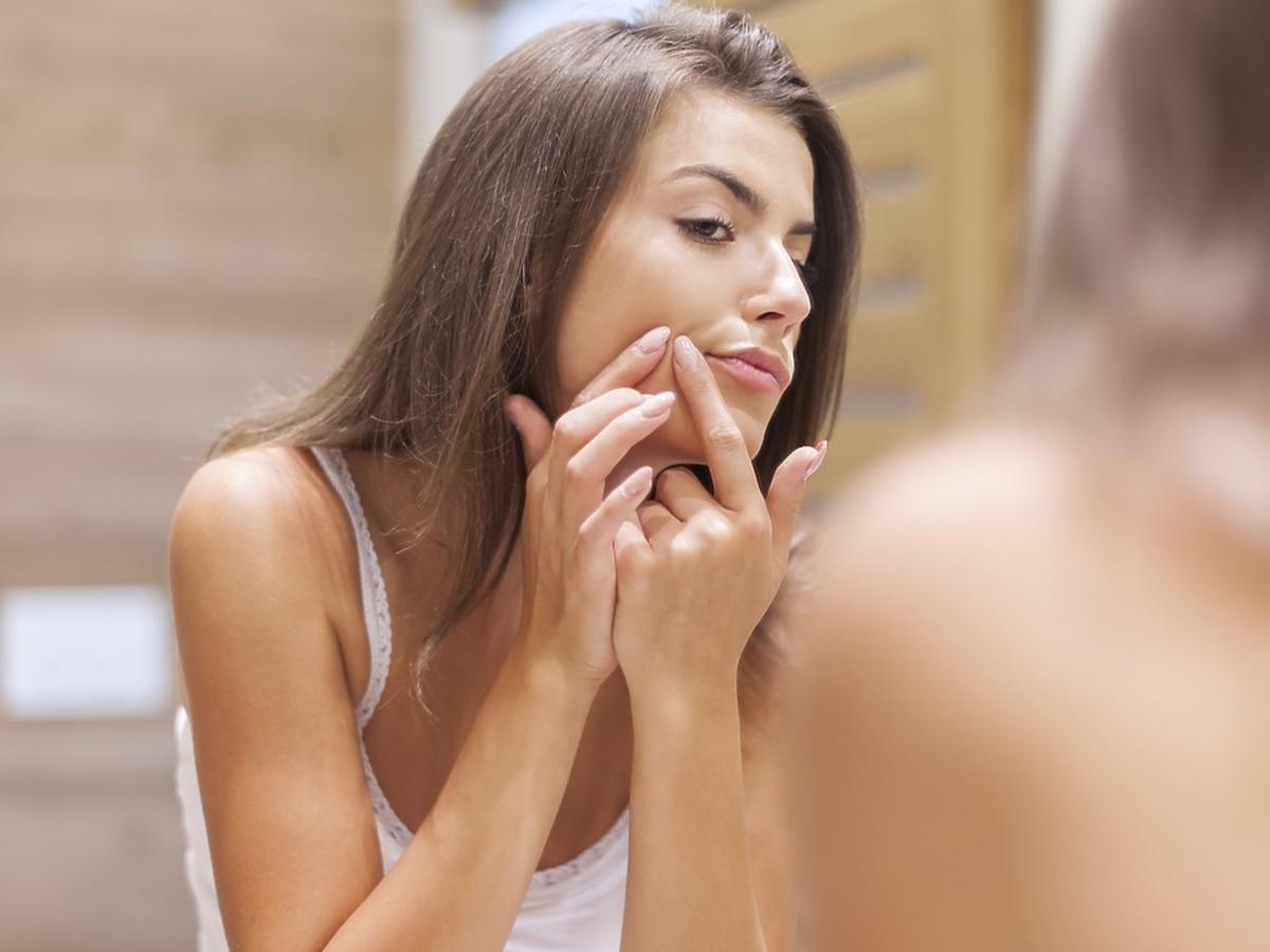 dziewczyna z trądzikiem patrzy w lustro