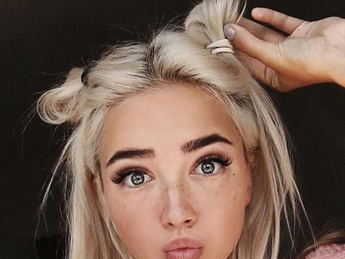 Dziewczyna ze związanymi blond włosami w różowym swetrze i z piegami na twarzy robi selfie
