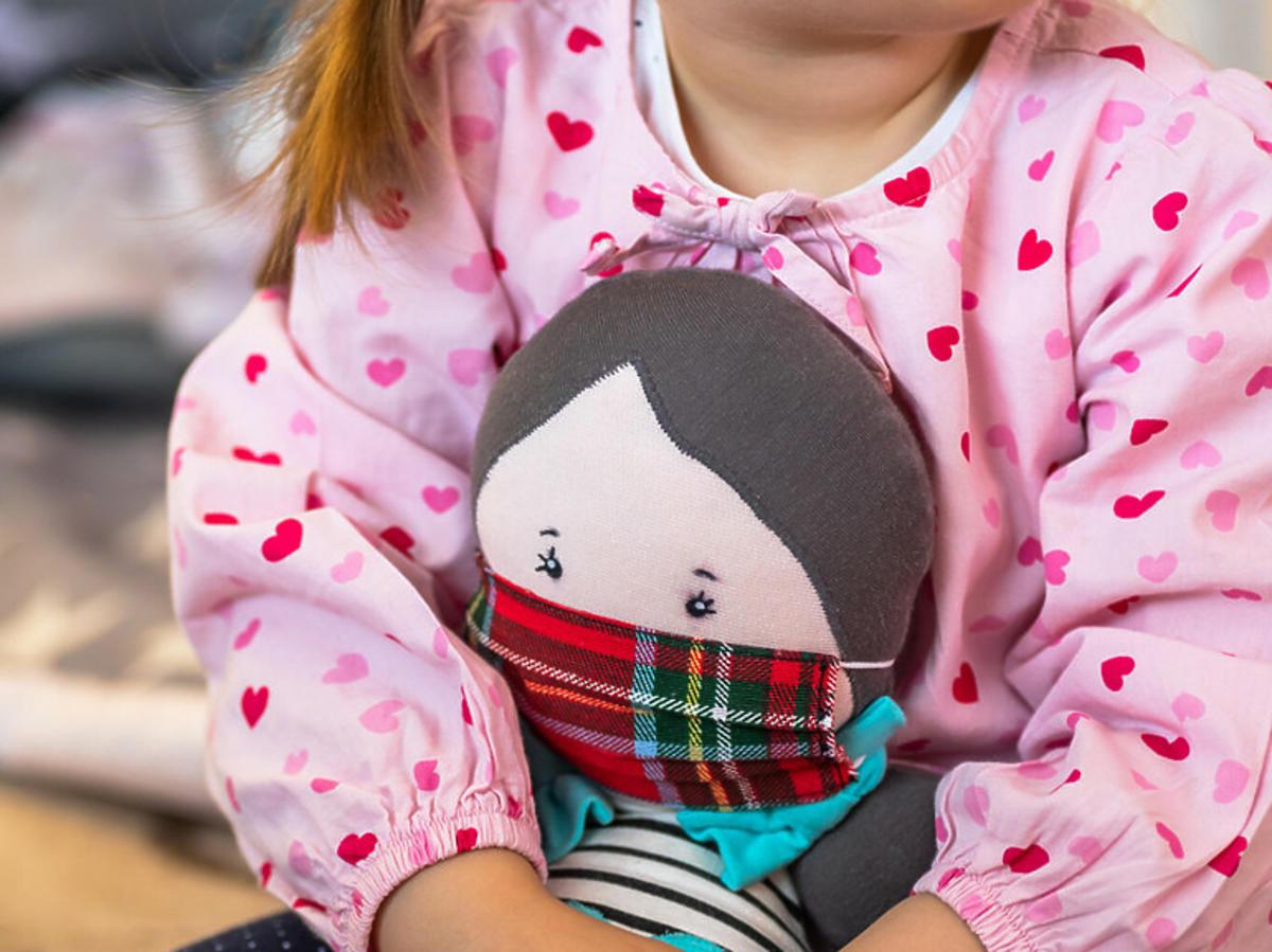 Dziewczynka trzymająca lalkę z maseczką na głowie