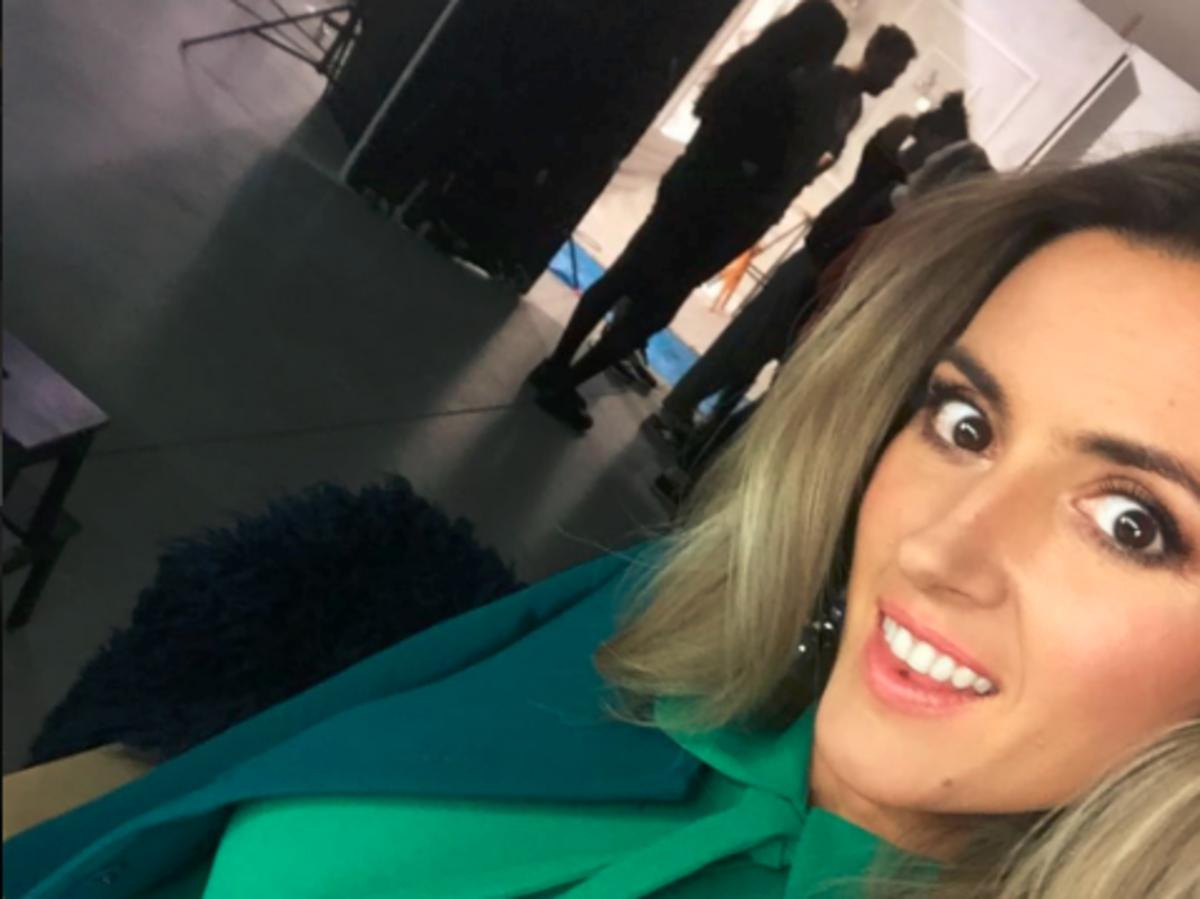 Karolina Szostak w blond włosach, zielonej bluzce i wzorzystej spódnicy