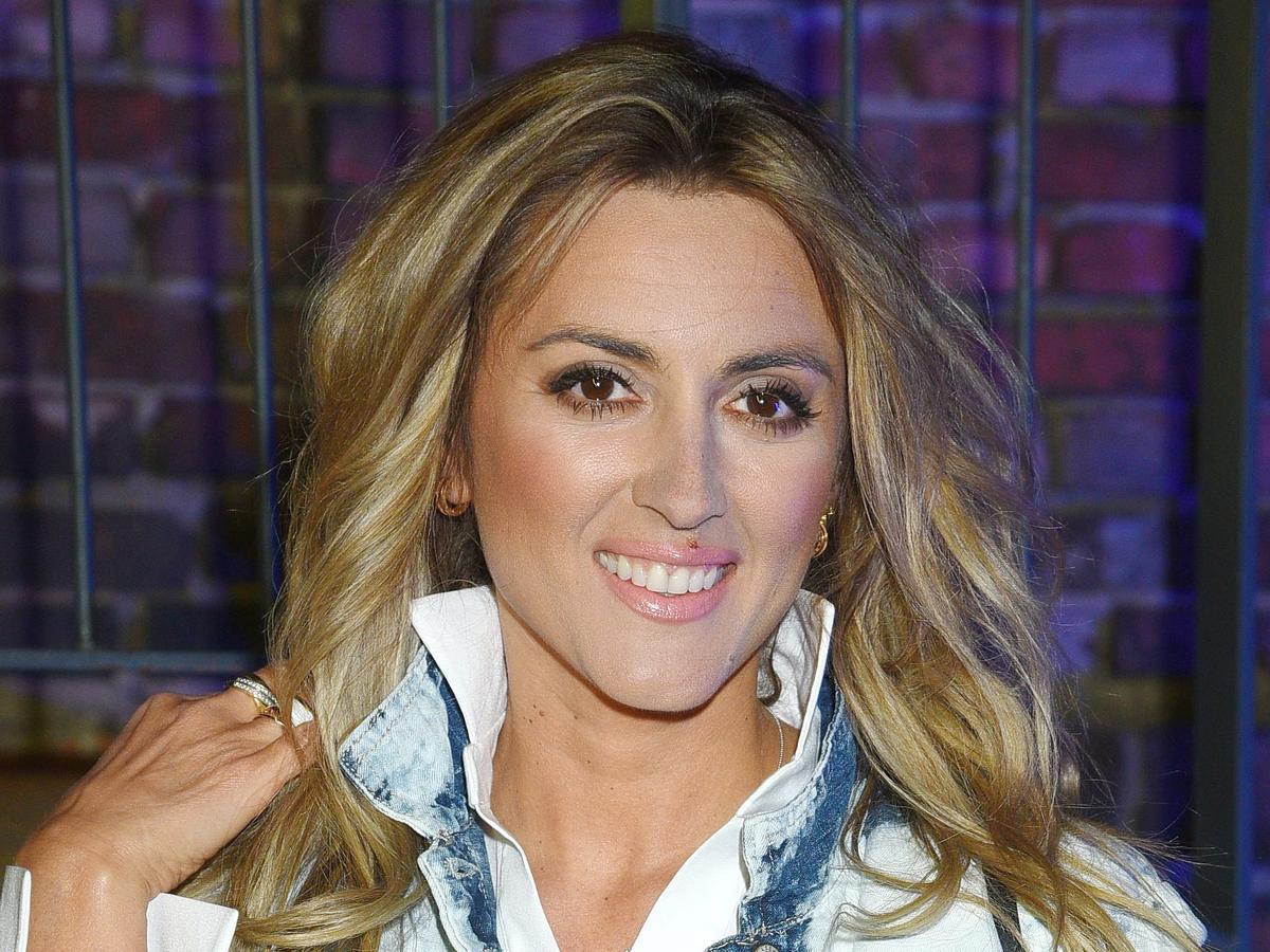 Karolina Szostak w rozpuszczonych włosach, białej koszuli i dżinsowej kurtce