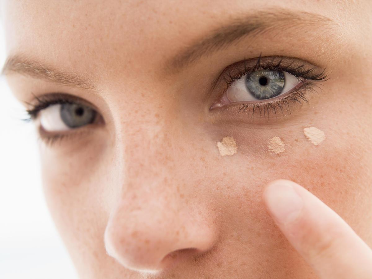 kobieta aplikuje korektor pod oczy