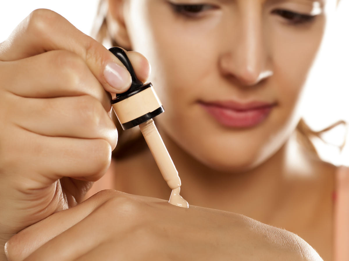 kobieta aplikuje podkład z pipetką