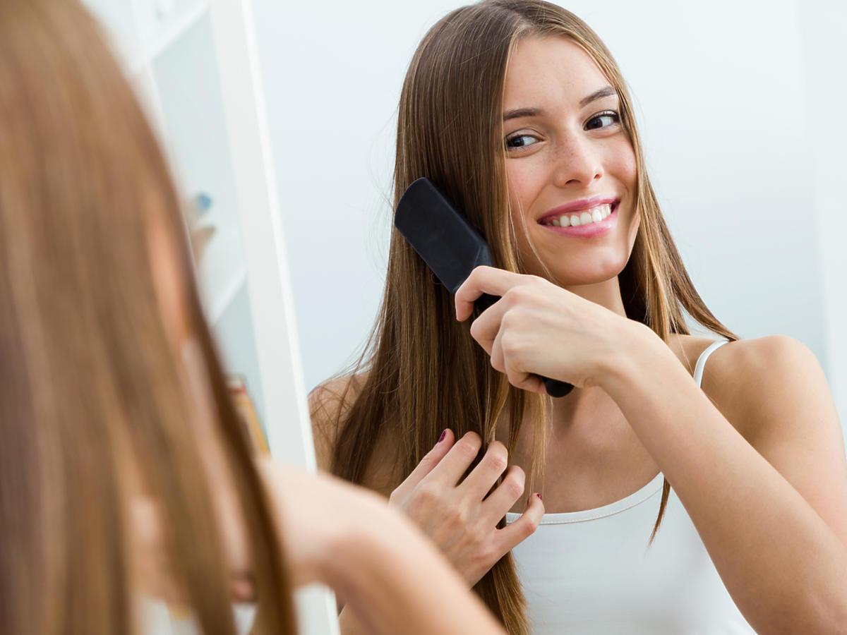 kobieta czesze włosy przed lustrem
