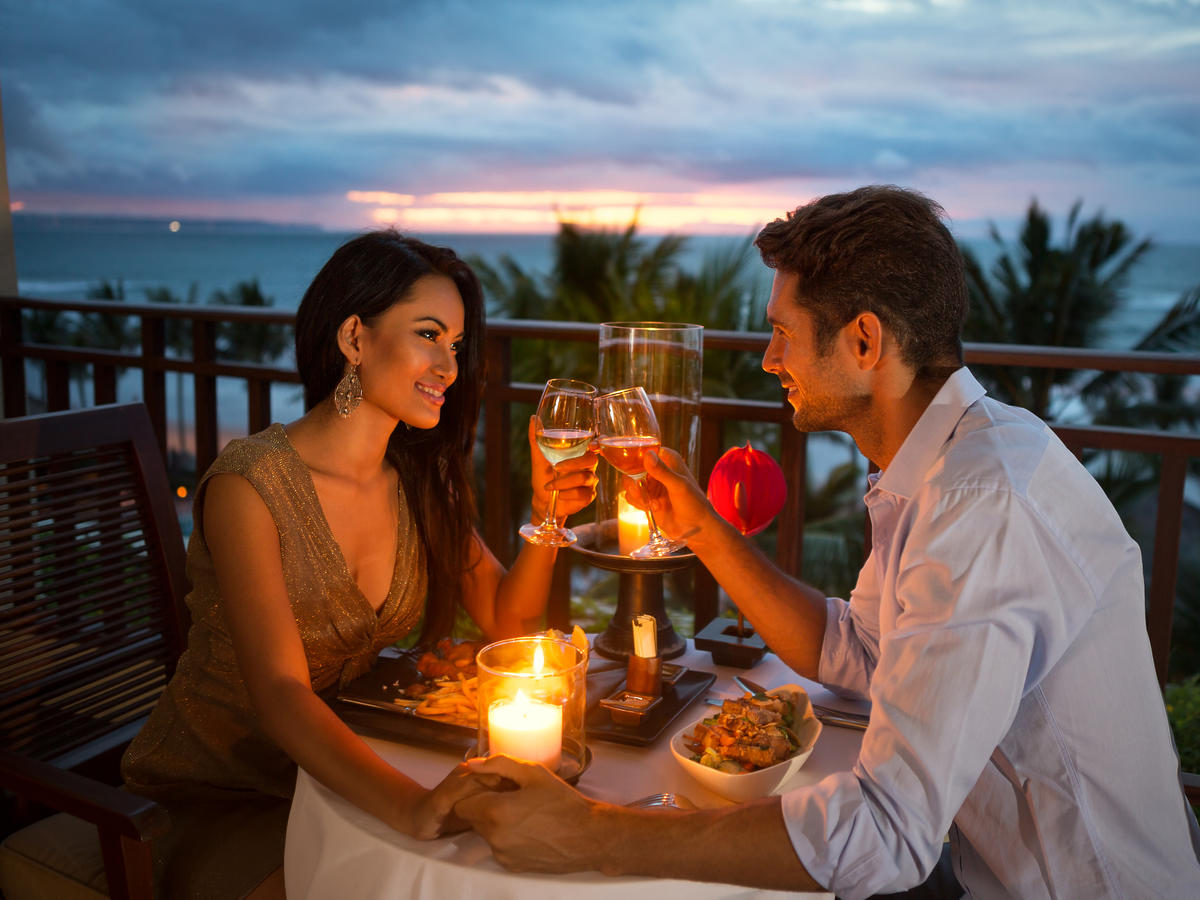 Kobieta i mężczyzna przy stole z jedzeniem wznoszą toast lampką szampana