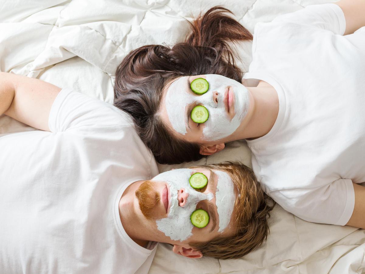 Kobieta i mężczyzna ubrani na biało leżą w łóżku z białą pościelą z maseczkami na twarzy i ogórkiem na oczach