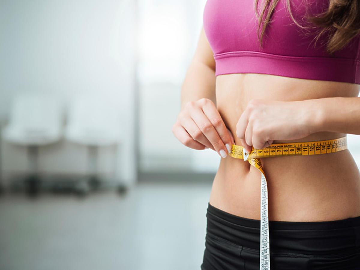 Kobieta mierząca talie po diecie na szybkie schudnięcie