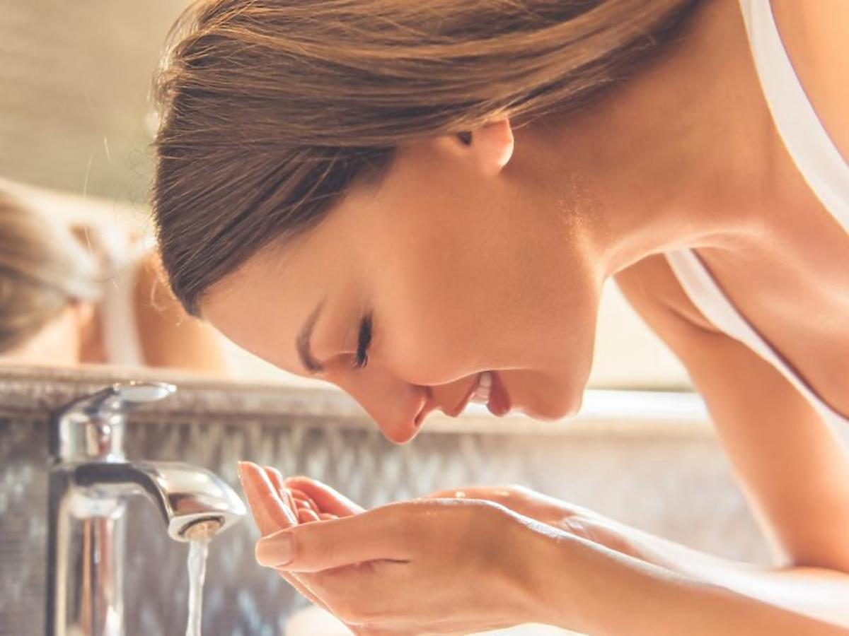 kobieta myjąca twarz