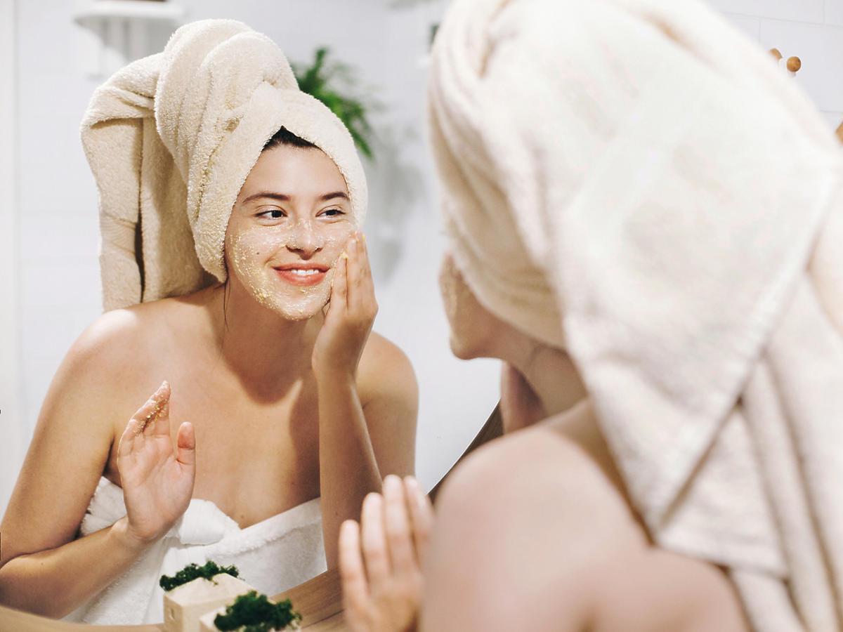 kobieta nakłada na twarz peeling AA