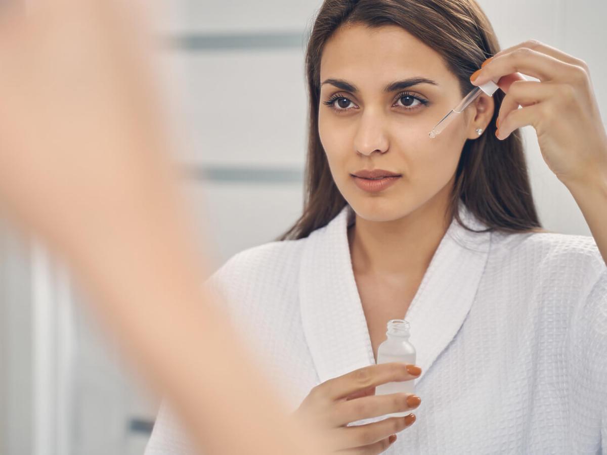 kobieta nakłada serum z kwasem ferulowym