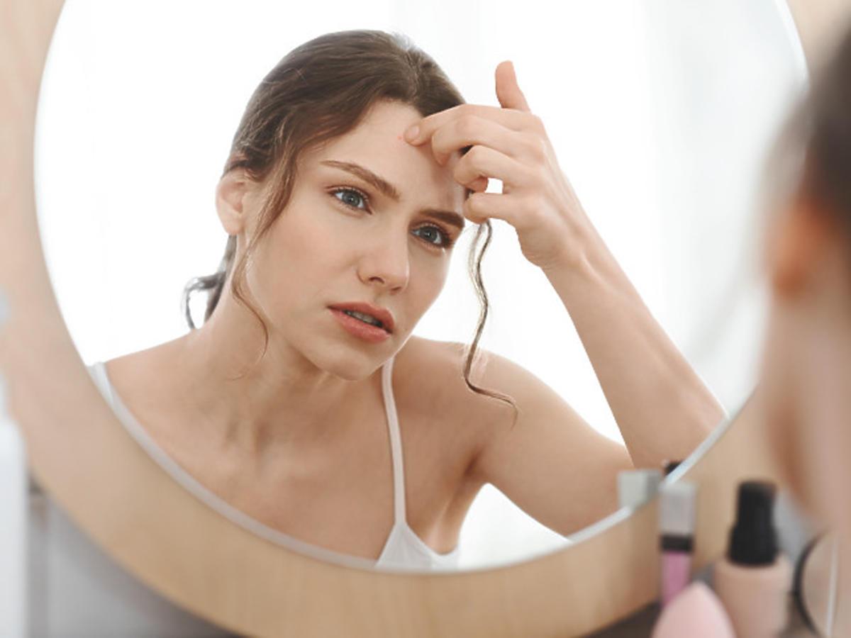 kobieta oglądająca swoje czoło