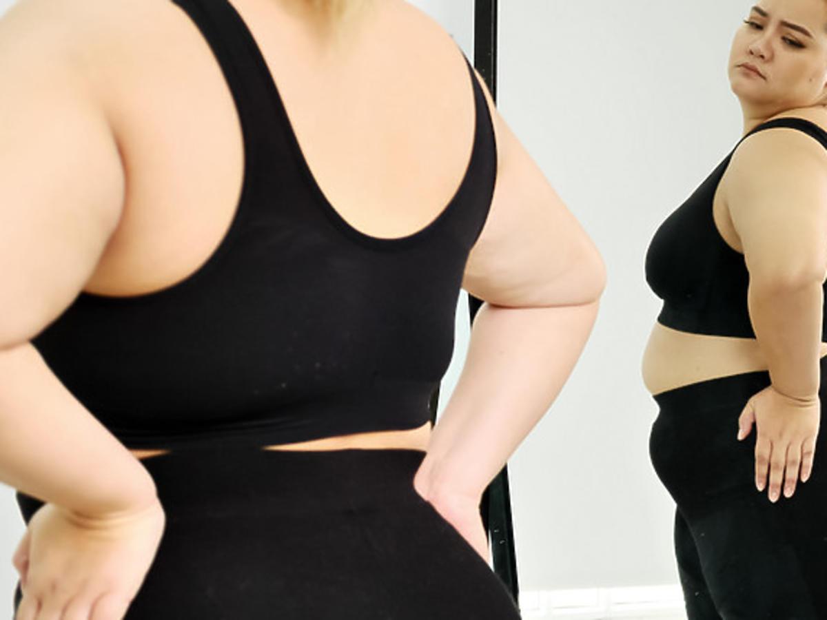 kobieta plus sile stojąca przed lustrem