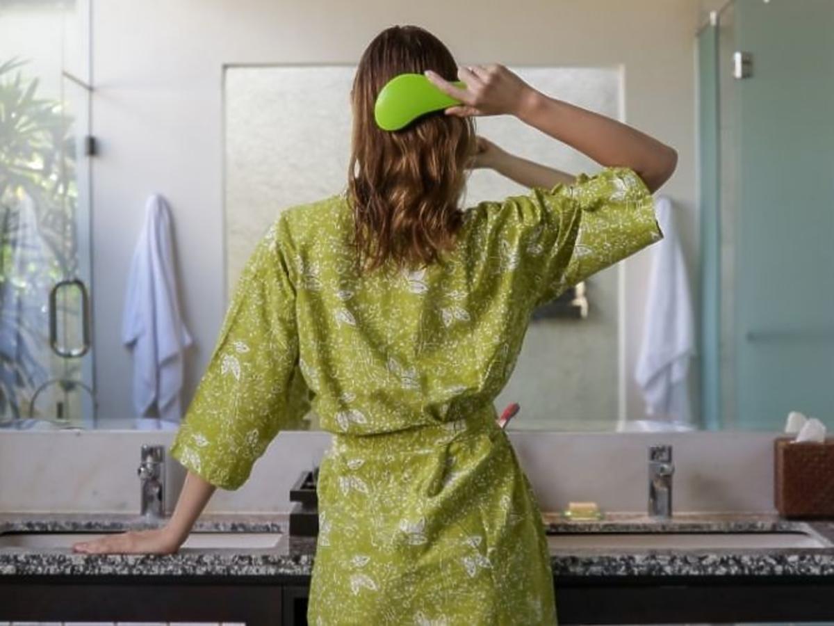 kobieta rozczesuje włosy szczotką