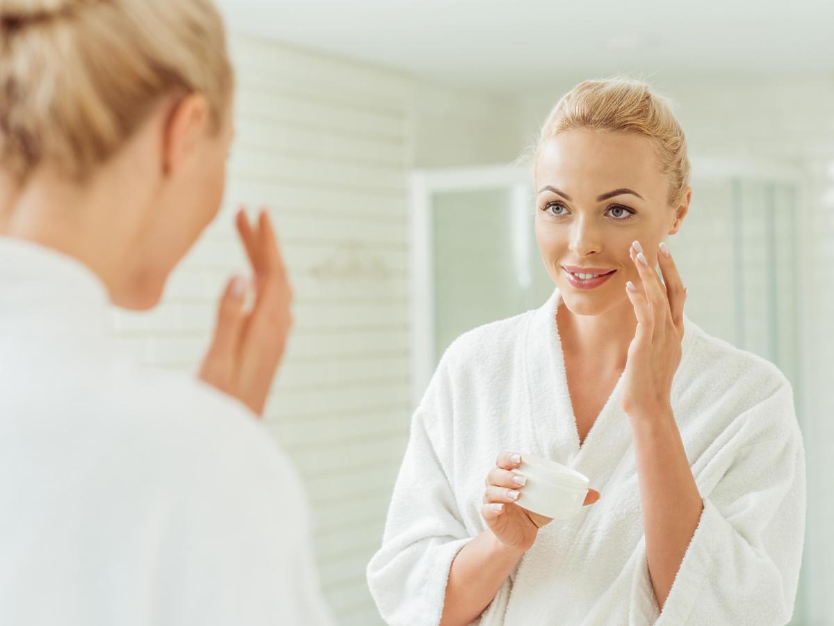 kobieta smarująca twarz przed lustrem
