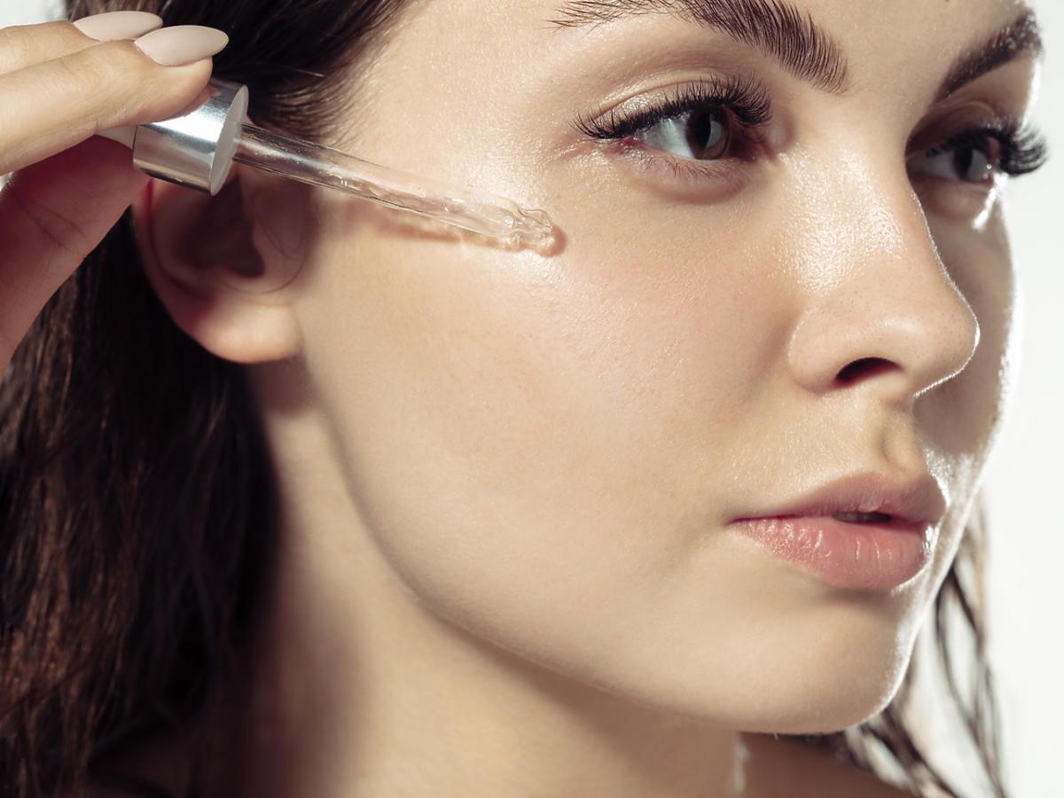 kobieta stosuje serum do twarzy z filtrem SPF 30