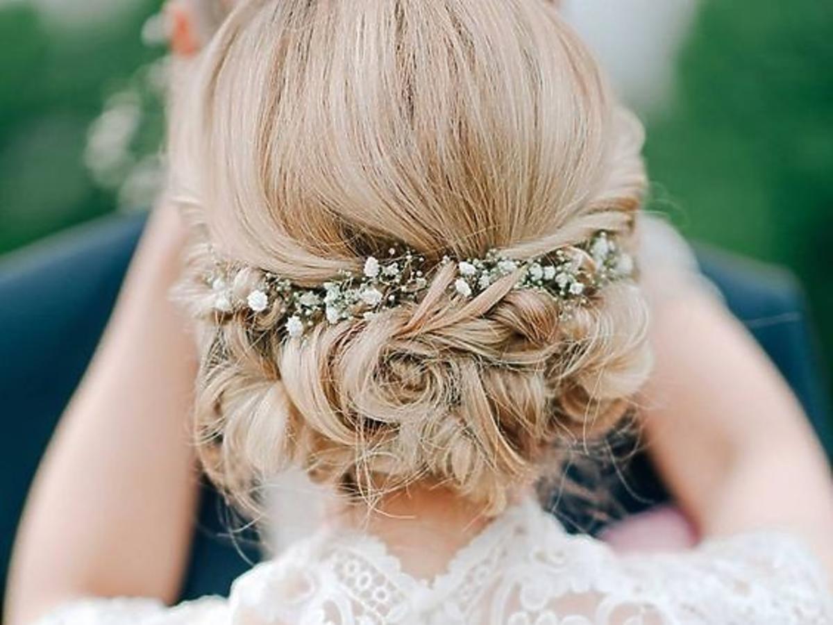 Kobieta w białej, koronkowej sukni ślubnej z blond włosami, upiętymi nad karkiem i ozdobionymi wsuwką