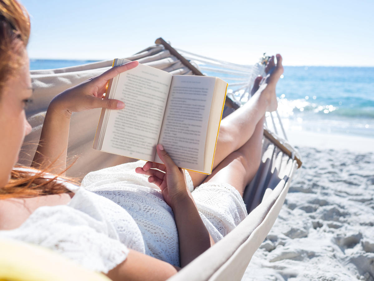 kobieta w hamaku z książką na plaży