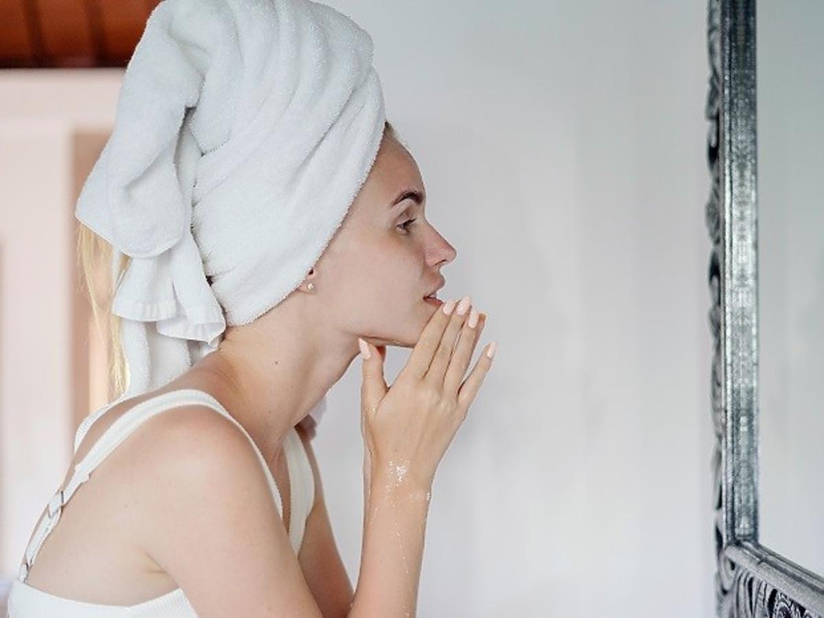 Kobieta w ręczniku na głowie, oczyszczająca twarz