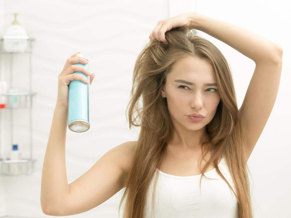 kobieta z lakierem do włosów