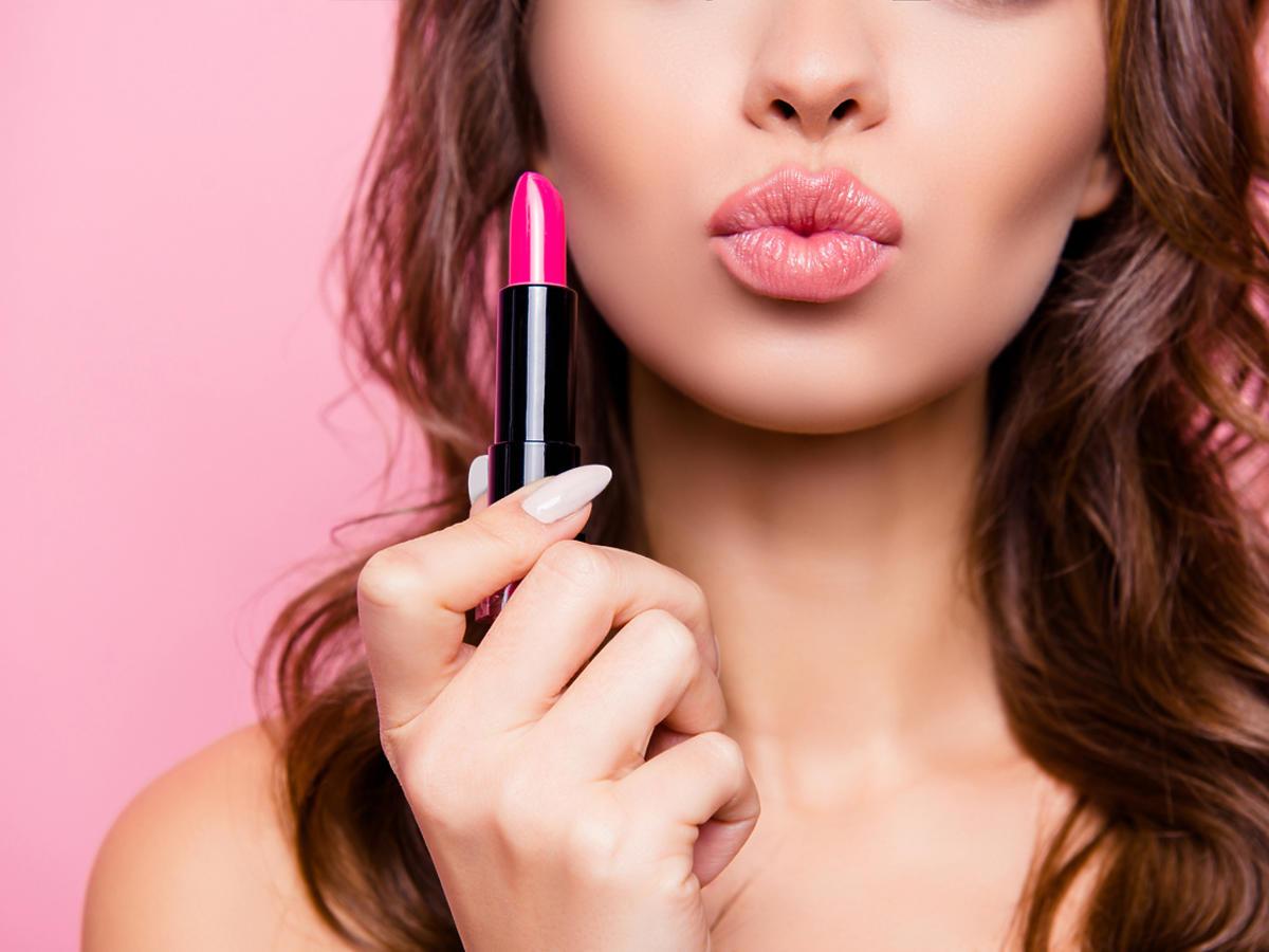kobieta z pomalowanymi ustami trzyma w ręce szminkę