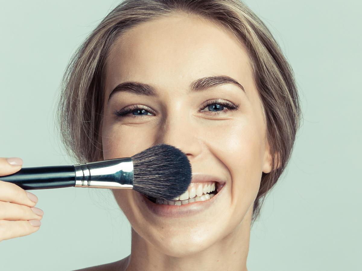 kobieta zasłania twarz pędzlem do malowania