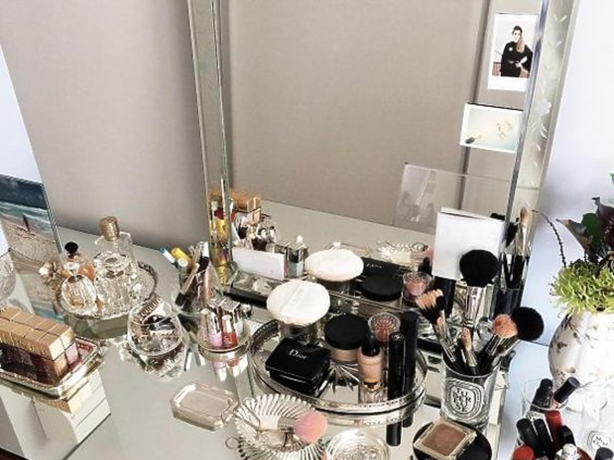 Kosmetyki ułożone na kobiecej toaletce w domu