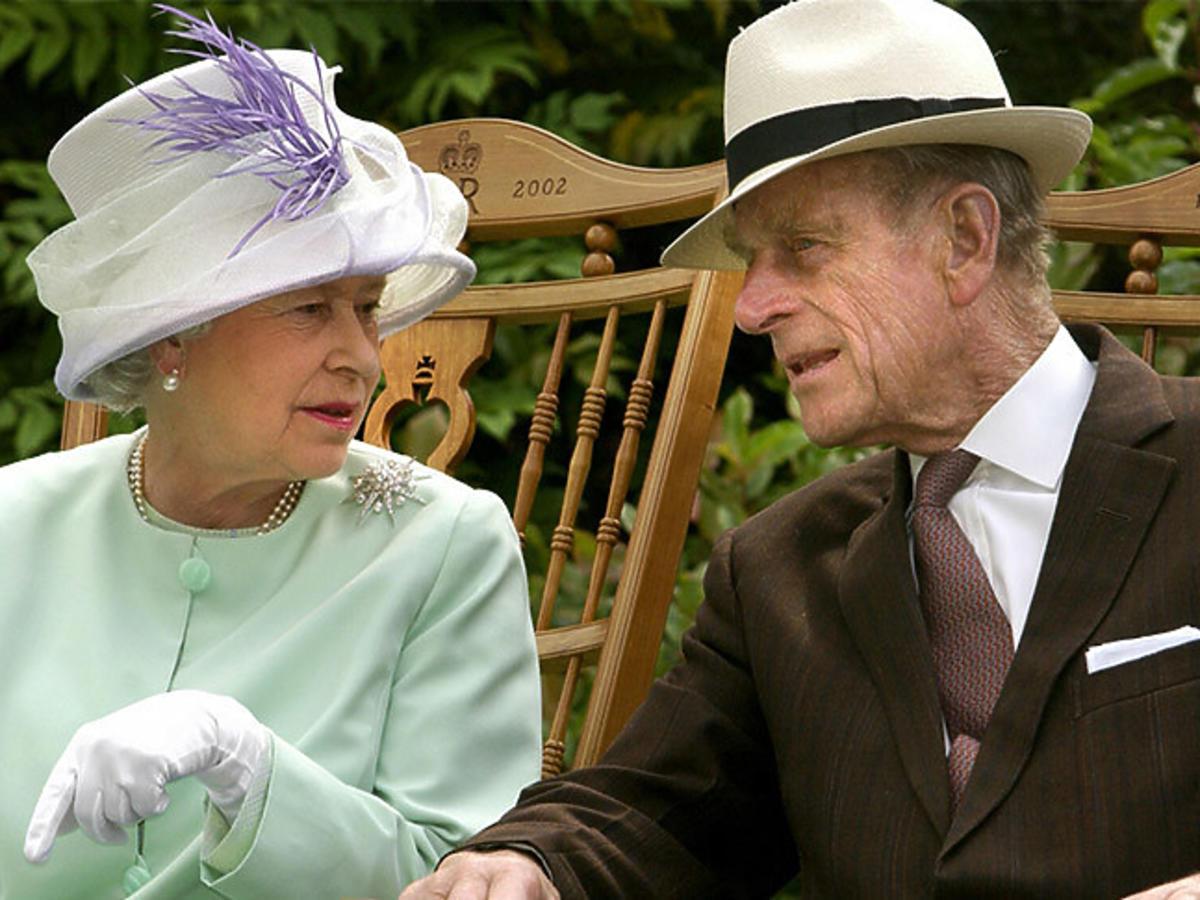 Królowa Elżbieta w miętowej kreacji spogląda na księcia Filipa