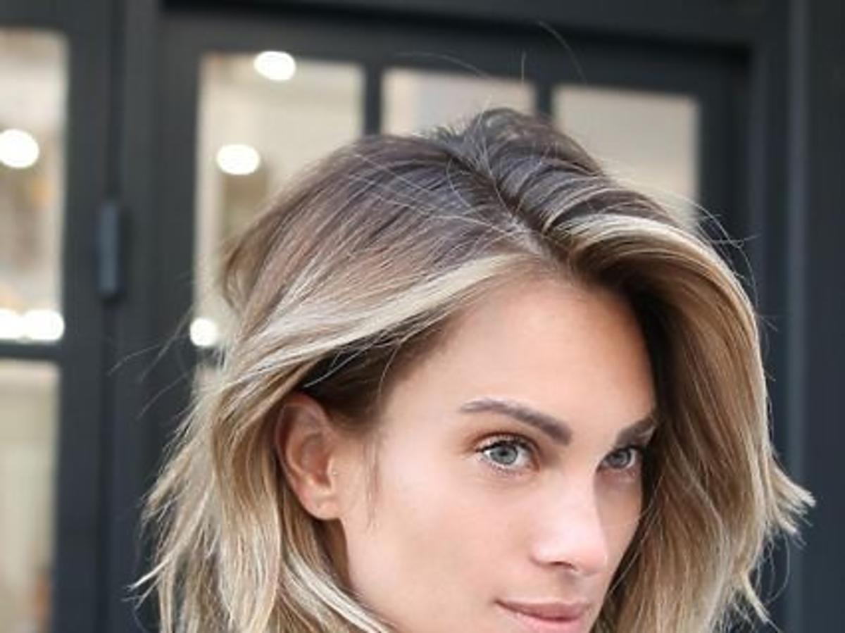 Ładna kobieta w krótkich włosach w kolorze blond z przeciągniętym odrostem pozuje prawym profilem do kamery na tle okien