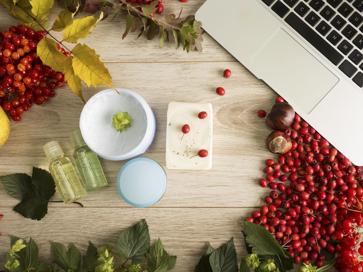 Laptop, jesienne liście i kosmetyki